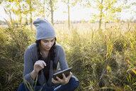 Woman using digital tablet in field - HEROF32632