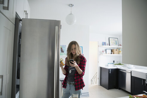 Woman texting at refrigerator in kitchen - HEROF32638