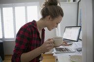 Woman drinking coffee using digital tablet - HEROF32641