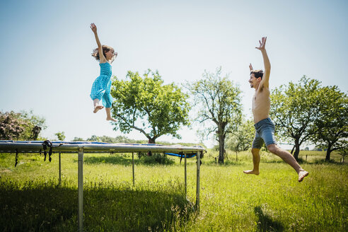 Playful father and daughter jumping on trampoline in sunny summer back yard - FSIF03794