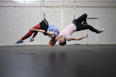 Modern aerialist dancers performing, hanging upside-down - FSIF03815