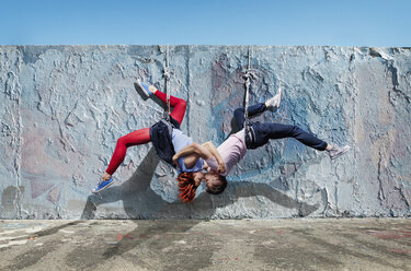 Modern aerialist dancers kissing, hanging upside-down - FSIF03824