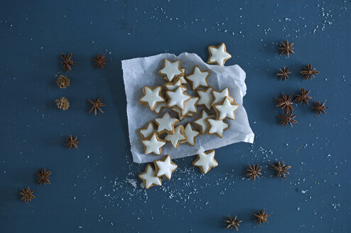Cinnamon stars, star anise and pine cones on blue ground - ASF06356