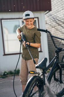 Boy washing bmx bike with pressure washer on yard - VPIF01183