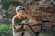 Boy with bmx bike using cell phone - VPIF01204