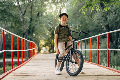 Portrait of smiling boy with bmx bike on bridge - VPIF01207