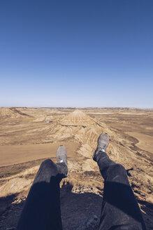 Spain, Navarra, Bardenas Reales, man's legs dangling above meager landscape - RSGF00127