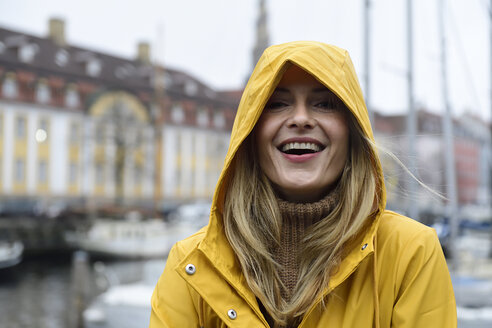 Denmark, Copenhagen, portrait of happy woman at city harbour in rainy weather - ECPF00624