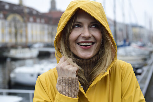 Denmark, Copenhagen, portrait of happy woman at city harbour in rainy weather - ECPF00627