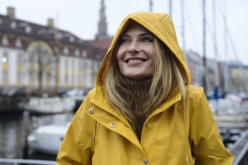 Denmark, Copenhagen, portrait of happy woman at city harbour in rainy weather - ECPF00630