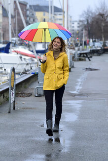 Denmark, Copenhagen, happy woman with colourful umbrella strolling at city harbour - ECPF00633