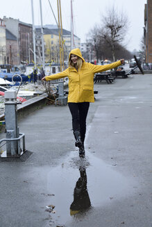 Denmark, Copenhagen, happy woman jumping in puddles at city harbour - ECPF00639