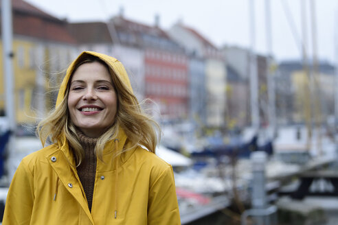 Denmark, Copenhagen, portrait of happy woman at city harbour in rainy weather - ECPF00642