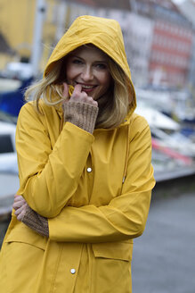 Denmark, Copenhagen, portrait of happy woman at city harbour in rainy weather - ECPF00645