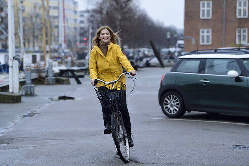 Denmark, Copenhagen, happy woman riding bicycle on waterfront promenade in rainy weather - ECPF00651