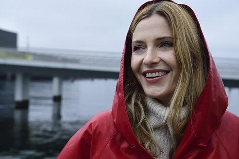Denmark, Copenhagen, portrait of happy woman at the waterfront in rainy weather - ECPF00657