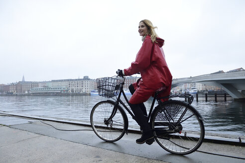 Denmark, Copenhagen, happy woman riding bicycle at the waterfront in rainy weather - ECPF00660