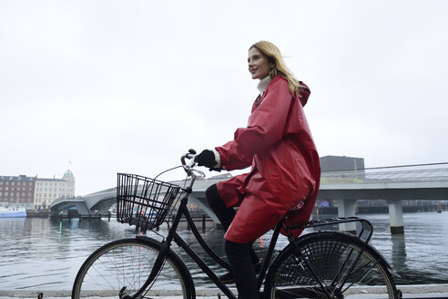 Denmark, Copenhagen, woman riding bicycle at the waterfront in rainy weather - ECPF00663
