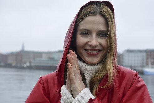 Denmark, Copenhagen, portrait of happy woman at the waterfront in rainy weather - ECPF00666