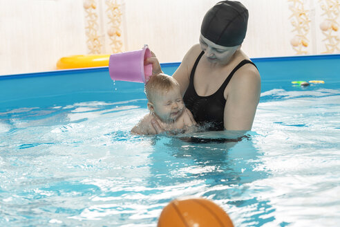 Baby swimming, mother with daughter in swimming pool, mother pouring water over head - VGF00263