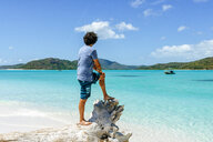 Australia, Queensland, Whitsunday Island, man standing on log at Whitehaven Beach - KIJF02482