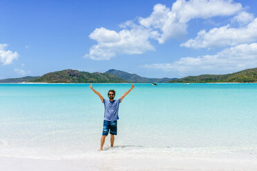 Australia, Queensland, Whitsunday Island, man with raised arms standing at Whitehaven Beach - KIJF02485