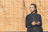 Portrait of sporty young woman with earphones and cell phone at a brick wall - WPEF01433
