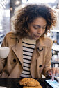 Woman using cell phone in a cafe - FMOF00480