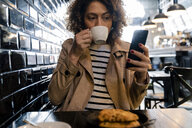 Woman drinking coffee and using cell phone in a cafe - FMOF00483