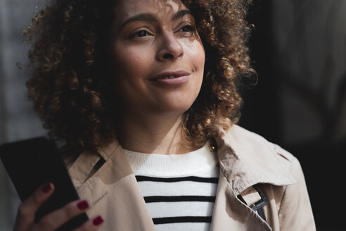 Portrait of smiling woman holding cell phone - FMOF00495