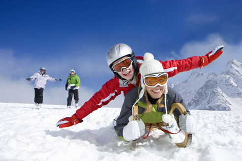 Family laying on sled in snow on mountain top - JUIF00701