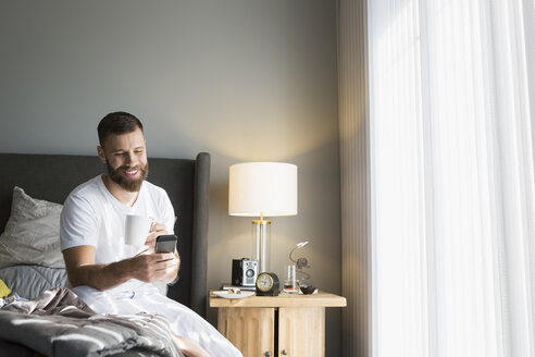 Smiling man drinking coffee and using cell phone on morning bed - HEROF32755