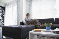Woman relaxing with blanket using digital tablet on living room sofa - HEROF32761