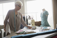 Senior woman seamstress viewing fabric in home office - HEROF32764