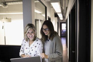 Smiling businesswomen using laptop in office corridor - HEROF32818