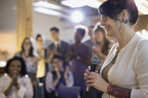 Smiling businesswoman with microphone leading conference meeting - HEROF32821