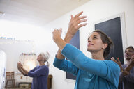 Serene woman practicing tai chi in exercise class - HEROF32839
