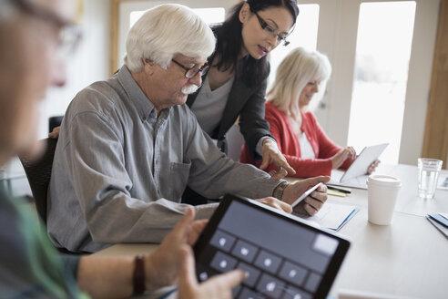 Teacher helping senior students using digital tablets in classroom - HEROF32857
