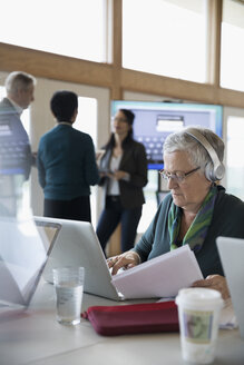 Senior woman student with headphones using laptop in classroom - HEROF32872