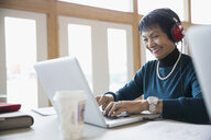 Smiling senior woman student with headphones using laptop in classroom - HEROF32875