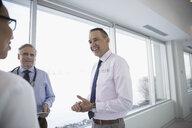 Smiling doctors consulting in clinic corridor - HEROF32887