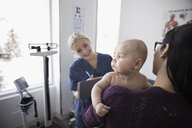 Smiling female nurse talking with mother and baby son in clinic examination room - HEROF32893