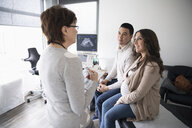 Female obstetrician talking with pregnant couple in clinic examination room - HEROF32957