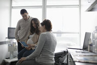 Female obstetrician talking with pregnant couple in clinic examination room - HEROF33044