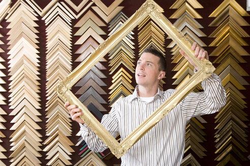 Clerk lifting gold frame in frame shop - JUIF00713