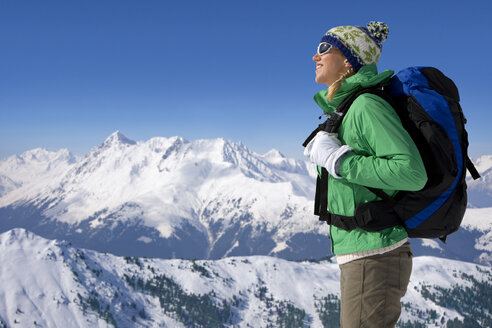 Woman with backpack on snowy mountain - JUIF00728