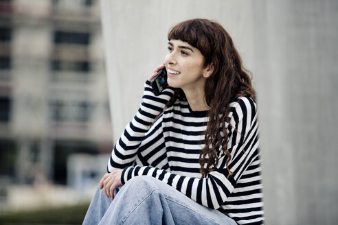 young woman wearing striped shirt, using smartphone - FLLF00086