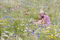 Mother and daughter looking at book in wildflower field - JUIF00786