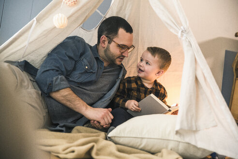 Father and son reading a book together in tent at home - UUF16855