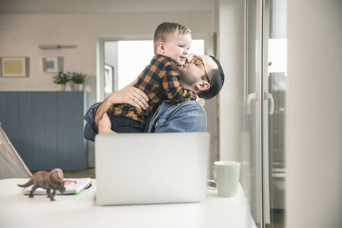 Father sitting at table in home office hugging son - UUF16864